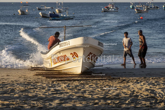 Puerto Escondido beach, Oaxaca, Mexico, Fishing boats arriving at dawn to sell fresly caught fish. The captain steers the boat at full speed towards the beach while the crew lays down sticks to create a ramp, beaching the boat on dry land where buyers can surround it to inspect the catch. - Jim West - 2020-02-04