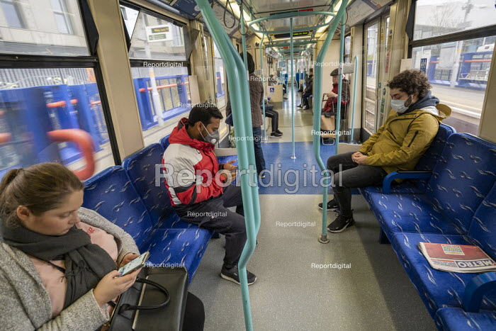 Commuters with face masks, Docklands Light Railway to protect against Coronavirus , East London. - Jess Hurd - 2020-03-18