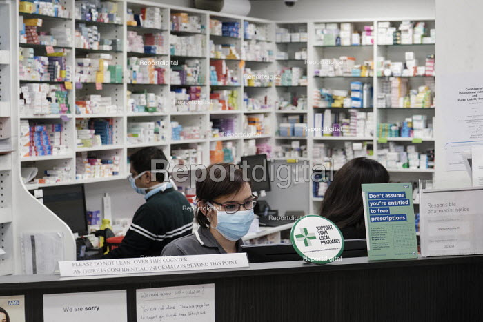 Coronavirus pandemic. Pharmacists working in facemasks and disposible gloves, pharmacy, Putney, London - Duncan Phillips - 2020-03-23