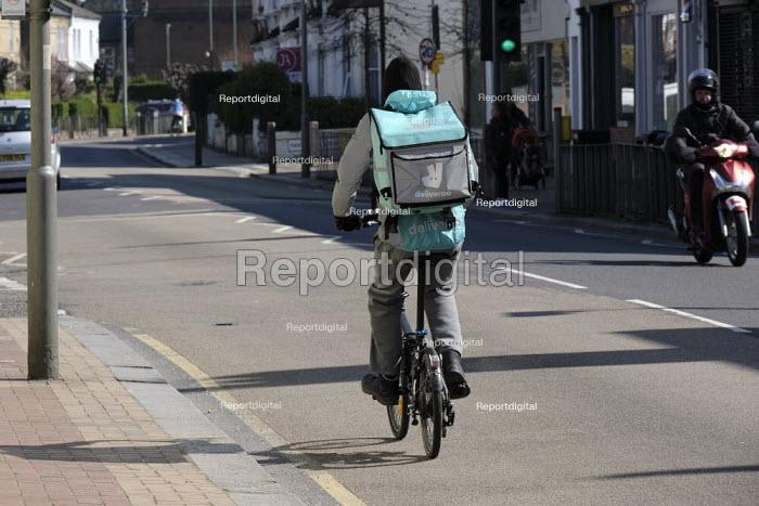 Coronavirus pandemic, Deliveroo rider working during lockdown, Putney, London - Duncan Phillips - 2020-03-26