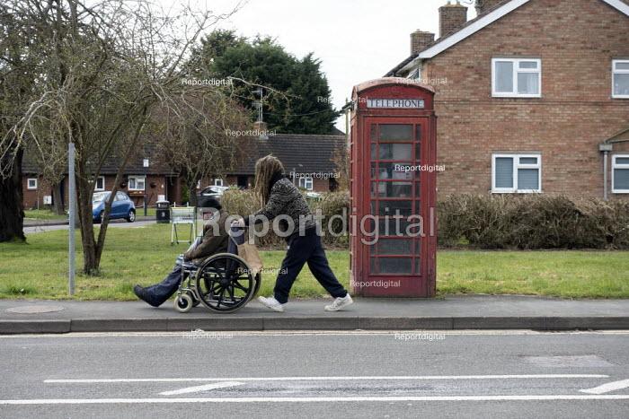 Coronavirus pandemic, young carer taking a disabled man in a wheelchair to the supermarket, Stratford Upon Avon, Warwickshire - John Harris - 2020-03-31