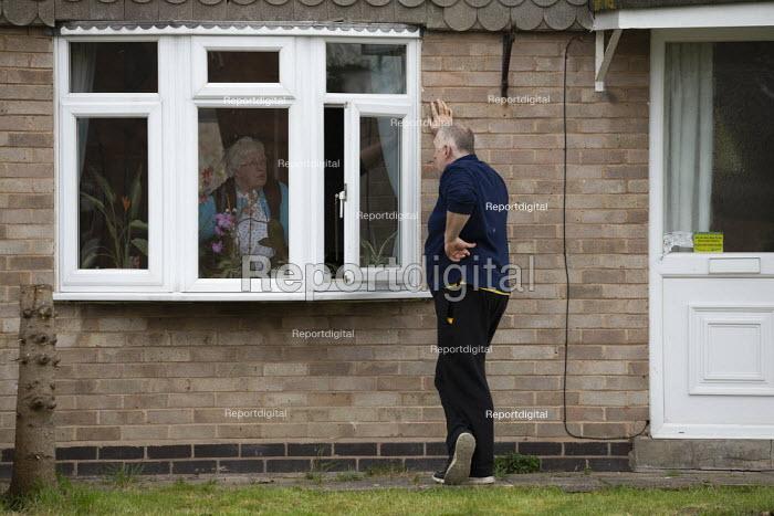Coronavirus Pandemic. Conversation through an open window. Man talking to an elderly woman maintaining social distance during the lockdown - John Harris - 2020-03-31