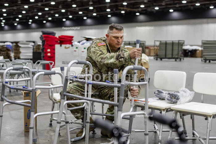 Detroit, Michigan USA. Emergency field hospital under construction, TCF convention center. The 1,000-bed hospital will care for Covid-19 patients A member of the Michigan National Guard assembling walkers. - Jim West - 2020-04-06