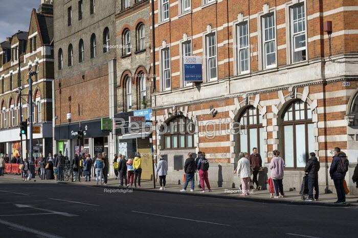 Coronavirus pandemic. Queuing outside Sainsburys Supermarket, Kilburn, London - Philip Wolmuth - 2020-04-06