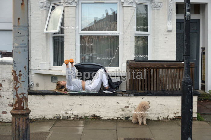 Covid-19 pandemic lockdown. Woman exercising with weights outside her flat in West Hampstead, London. - Philip Wolmuth - 2020-04-30