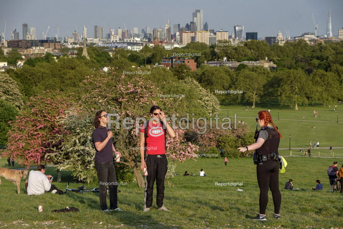 Coronavirus Pandemic. Police officer ordering sunbathers to take exercise or leave the park. Primrose Hill, London, where lockdown rules regarding social distancing, sunbathing and picnicing are not consistently observed. - Philip Wolmuth - 2020-05-07