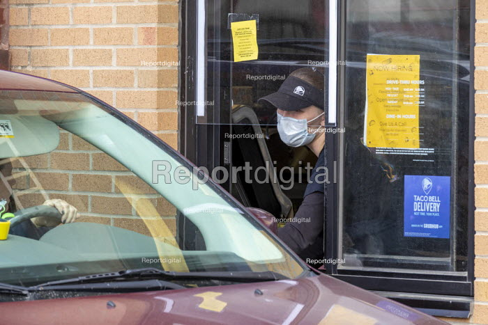 Michigan, USA. Taco Bell worker delivering an order at the drive through window. Due to the coronavirus pandemic, customers are not allowed inside the fast food restaurant. Workers at this restaurant are demanding that the company do more to protect them and customers from the coronavirus pandemic. They delivered a petition to management demanding: more staff to keep the restaurant clean; daily health screening of workers; a month's paid sick leave for anyone exposed to Covid-19 and $3 hour hazard pay. - Jim West - 2020-05-08