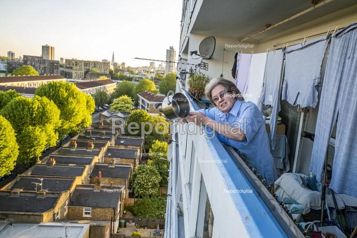 Coronavirus Pandemic. Clap for our Carers, Helen banging a saucepan, tower block, Tower Hamlets, East London - Jess Hurd - 2020-05-14