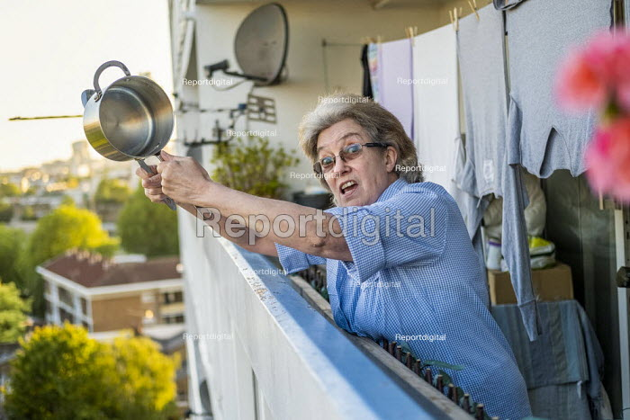 Coronavirus Pandemic. Clap for our Carers, Helen banging a saucepan, tower block, Tower Hamlets, East London - Jess Hurd - 2020-05-14