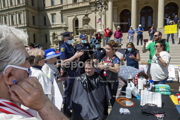 Lansing, Michigan US Coronavirus Pandemic. Barbers giving free haircuts on the lawn of the Michigan State Capitol in protest against emergency orders which keep many businesses closed. The protest, called Operation Haircut, was organized by the Michigan Conservative Coalition. State police warned barbers that they were violating the law, but did not make arrests. - Jim West - 2020-05-20