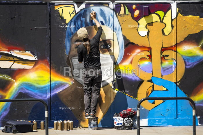 Coronavirus Pandemic: NHS heroes graffiti artist Owe1 painting a mural depicting health worker in PPE, Shoreditch, East London. - Jess Hurd - 2020-05-25