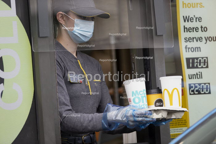 Coronavirus Pandemic. McDonald's reopening drive thru at all UK restaurants. Worker serving with face mask and screens, Stratford Upon Avon - John Harris - 2020-06-04