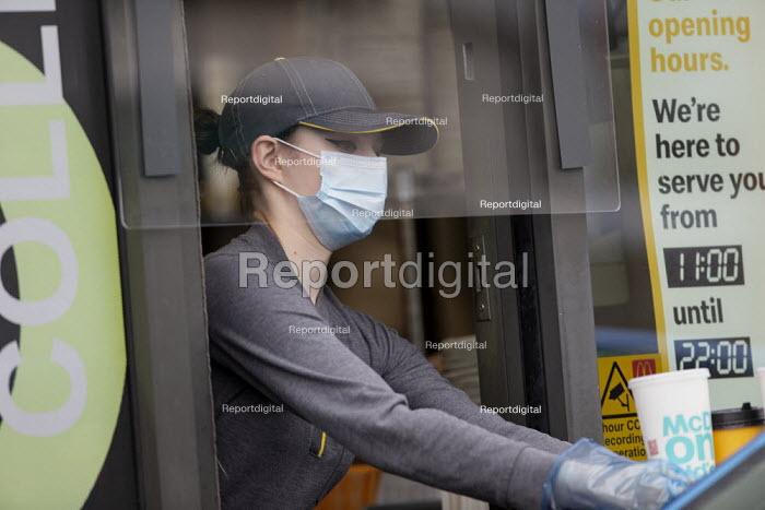 Coronavirus Pandemic. McDonald's reopening drive thru at all UK restaurants. Worker serving with face mask and screens, Stratford Upon Avon - John Harris - 2020-06-04