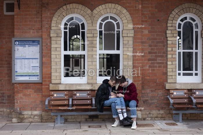 Coronavirus Pandemic. Lovers sitting on seats maked Do Not Sit Here, Stratford upon Avon Railway Station - John Harris - 2020-06-11