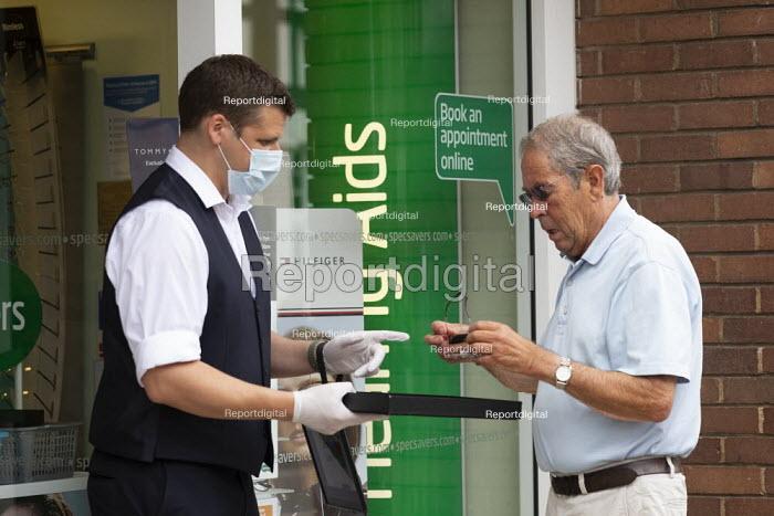 Spec Savers shopworker helping a customer in the shop doorway, Stratford Upon Avon - John Harris - 2020-06-16