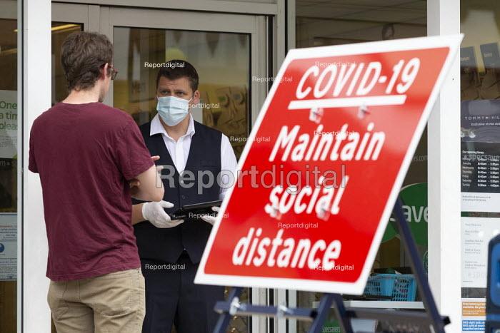 Spec Savers shopworker helping a customer in the shop doorway. Maintain Social Distance sign, Stratford Upon Avon - John Harris - 2020-06-16