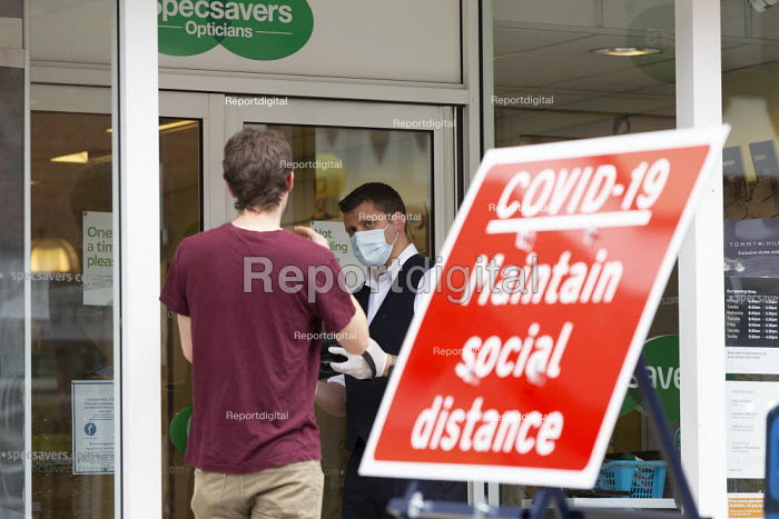 Spec Savers shopworker helping a customer in the shop doorway. Maintain Social Distance sign, Stratford Upon Avon - John Harris - 2020-06-16