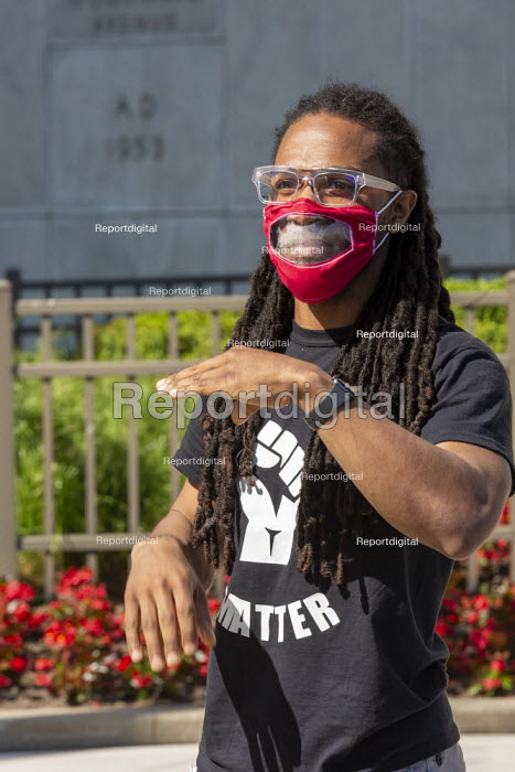 "Detroit, Michigan, USA. Deaf people at Black Disabled Lives Matter protest. Protest demanding that police funding be reallocated to mental health first responders and crisis intervention specialists. Teddy Dorsette III showing participants how to use sign language to say ""Black Lives Matter."" A transparent panel in his face mask allows others to read his lips. - Jim West - 2020-06-15"