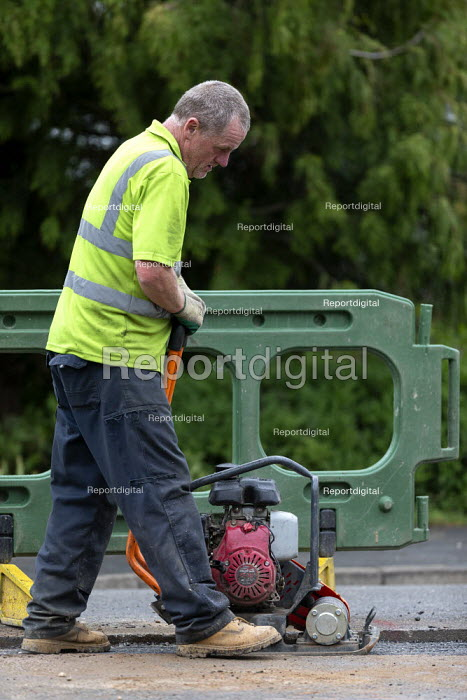 Workers tarmacing after installing a new gas main, using a plate compactor without ear defenders, Stratford-upon Avon - John Harris - 2020-06-19