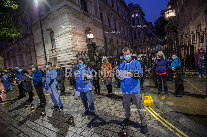 Sixty NHS staff and campaigners carrying a lantern each to represent the 60,000 deaths from Coronavirus. Reading the names of NHS staff who have died from coronavirus outside Downing Street. Organised by Keep Our NHS Public and Health Campaigns Together to mark the 72nd anniversary of the NHS and highlight the way the pandemic has exposed government underfunding of the service, Westminster, London. - Jess Hurd - 2020-07-03