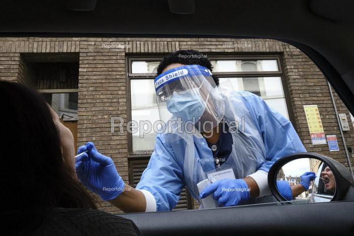 Coronavirus Pandemic. Woman being tested, drive thru testing Station, London. Mylocum Agency Nurse - Duncan Phillips - 2020-07-06