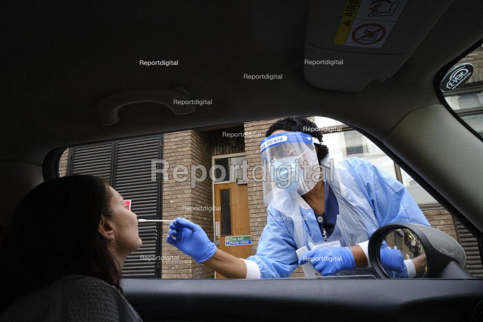 Coronavirus Pandemic. Woman being tested, drive thru testing Station, London. Mylocum Agency Nurse - Duncan Phillips - 2020-07-06