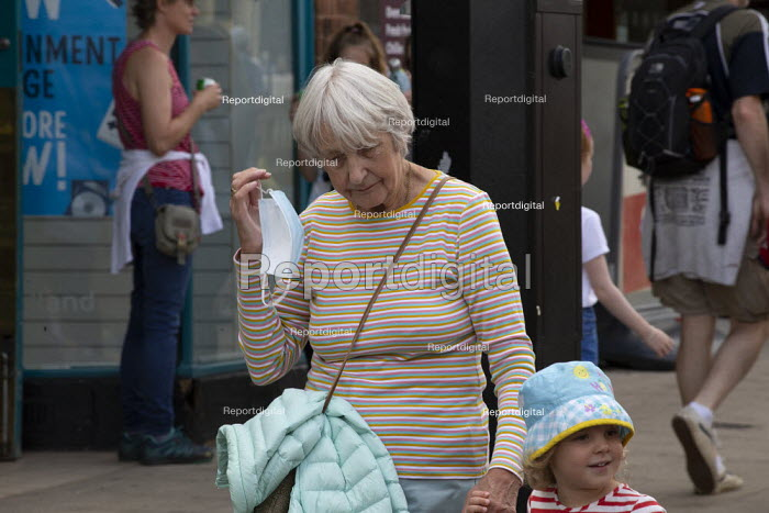 Mask up Friday, Shoppers removing her mask on leaving a shop, Stratford Upon Avon. Grandmother and child. - John Harris - 2020-07-24