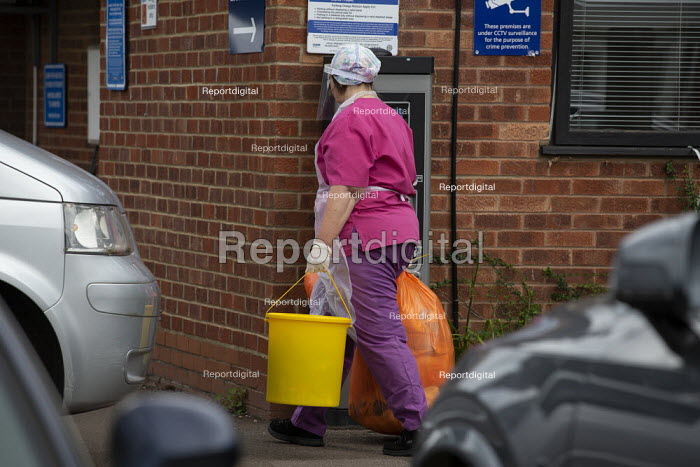 Cleaner in face sheild and protective gloves and gown removing waste, Medical Centre, Stratford Upon Avon - John Harris - 2020-07-29