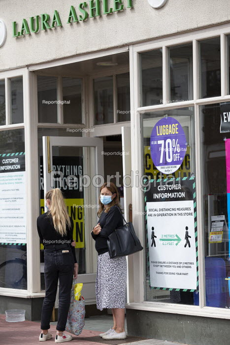 Shopper with face mask outside Laura Ashley closing down sale, Stratford Upon Avon - John Harris - 2020-07-29