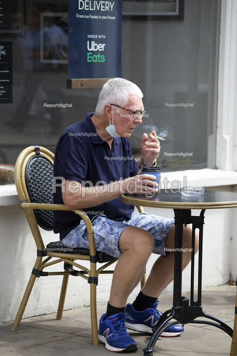 Older customer with face mask, smoking and drinking coffee at a table outside Caff� Nero, Stratford Upon Avon - John Harris - 2020-07-29