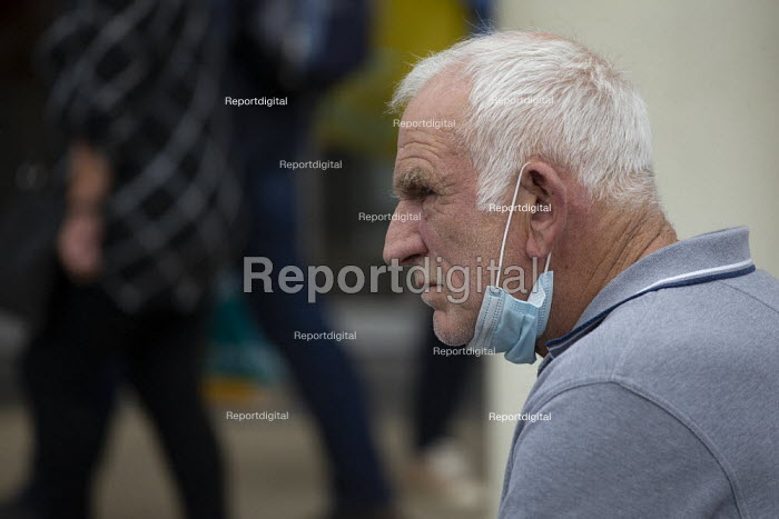 Unhappy elderly shopper with face mask down waiting outside Marks & Spencer, Stratford Upon Avon - John Harris - 2020-07-29