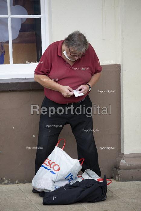 Elderly shopper with face mask down checking his receipt outside Marks & Spencer, Stratford Upon Avon - John Harris - 2020-07-29