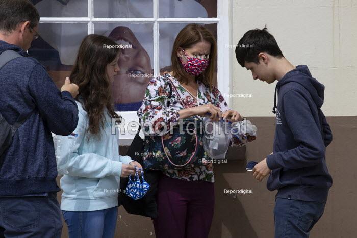 Mother carefully putting away family face masks into plastic bags outside Marks & Spencer, Stratford Upon Avon - John Harris - 2020-07-29