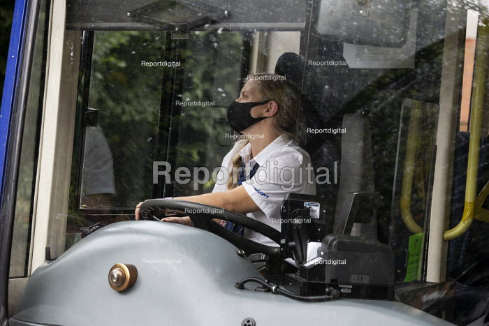 Woman bus driver, rural route, Warwickshire. Check mirrors before pulling out from a village bus stop - John Harris - 2020-08-05