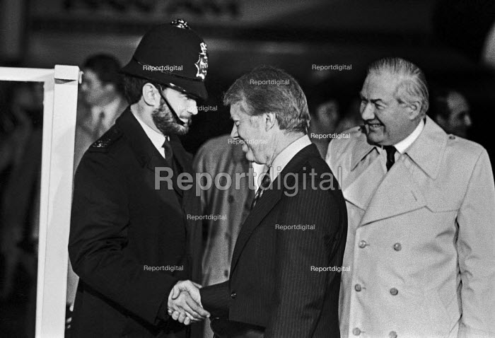 Jimmy Carter shanking hands with a policeman 1977 American president arriving at London Heathrow airport for a G7 meeting in the UK. Jim Callaghan introducing him to a line of VIPs - Peter Arkell - 1977-05-05