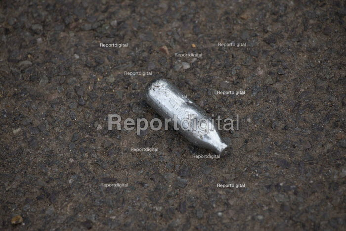 Discarded nitrous oxide cannister littering the street, Kineton, Warwickshire. Also called Laughing gas, the drug, when inhaled, gives a quick but brief high - John Harris - 2020-08-13