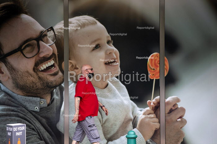 Shopper in a mask walking past image of happy father and son, OUTFIT, Central 6 Retail Park, Coventry. Do Your Bit sign - John Harris - 2020-08-15