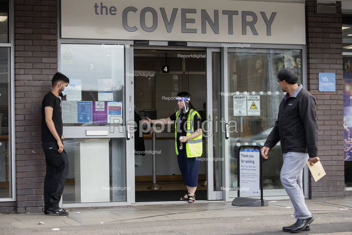 Bank worker in visor controlling customer queue, Coventry Building Society, Foleshill, Coventry. To maintain social distance - John Harris - 2020-08-15