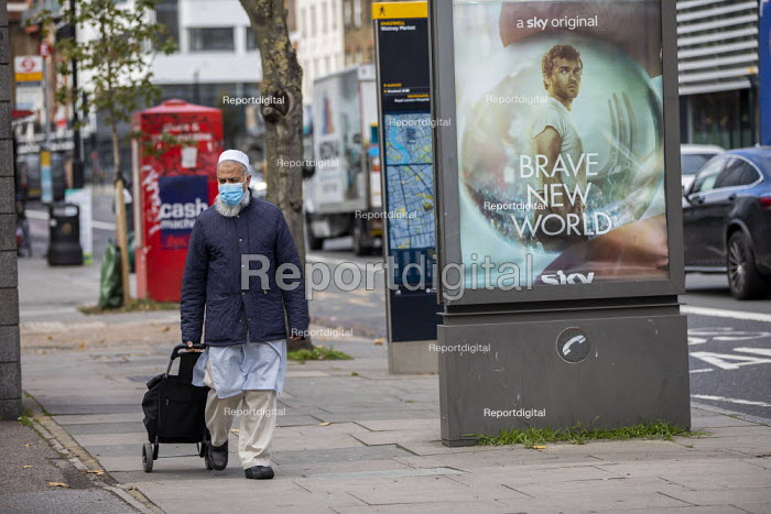 Shopper in mask and Brave New World Sky One advert, Watney Market, Stepney, East London. Film based on the Aldous Huxley groundbreaking 1932 novel, Brave New World which imagines a utopian society that has achieved peace and stability - Jess Hurd - 2020-10-15
