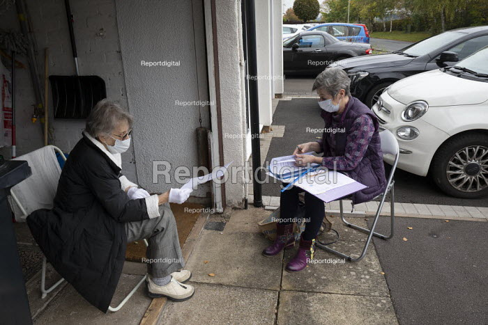Accountant and elderly client meeting in her open garage for safety. Halesowen. Meeting safely socially distanced with airflow to avoid infection during Coronavirus epedemic. Cilla Watts (Cooke and Watts) presenting a self employed psychotherapist Helen Lloyd with her annual accounts for approval - John Harris - 2020-10-16