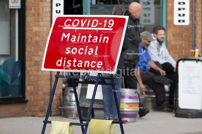 Covid-19 Maintain Social Distance sign, pub customers sitting outside, Stratford Upon Avon, Warwickshire - John Harris - 2020-10-07