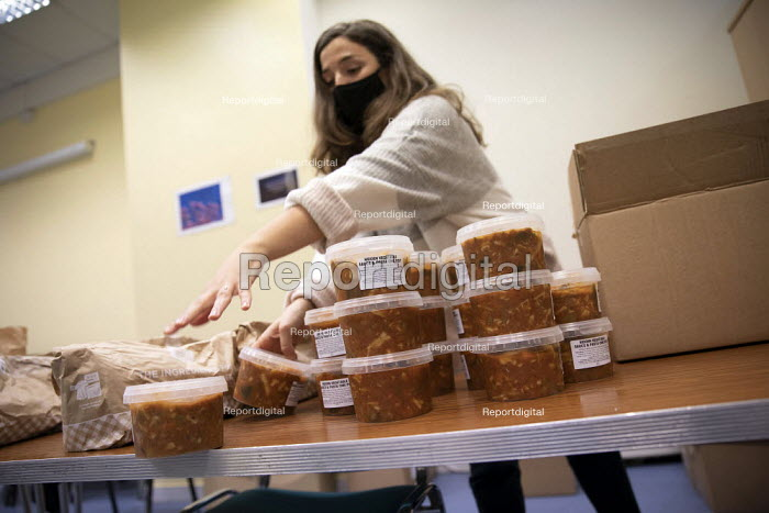 Volunteer making free school meals to help families in need. Tower Hamlets Council free school meals scheme to tackle hunger in children during the October half term school holiday. Gayton House, Tower Hamlets, East London - Jess Hurd - 2020-10-29