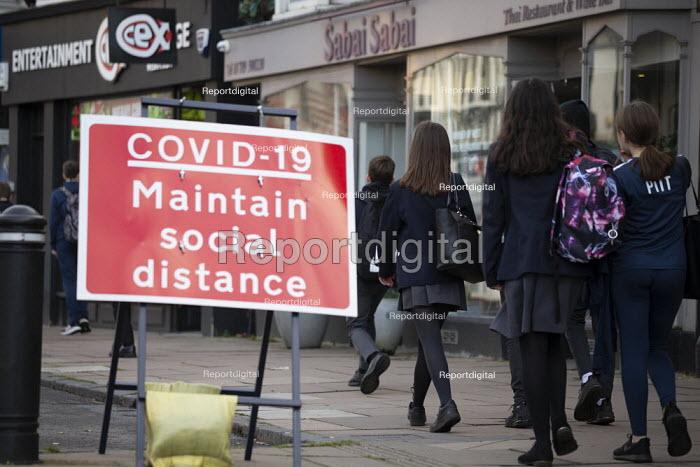 Pupils walking home by Covid-19 Maintain Social Distance sign, Stratford Upon Avon, Warwickshire - John Harris - 2020-11-10