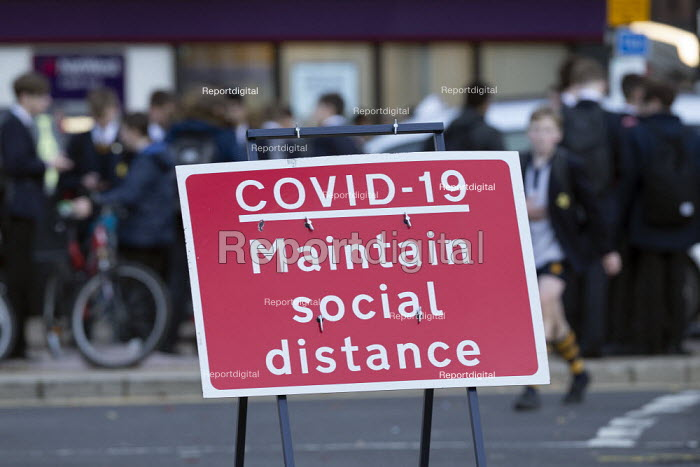 Pupils socialising, bus stop by Covid-19 Maintain Social Distance sign, Stratford Upon Avon, Warwickshire - John Harris - 2020-11-10