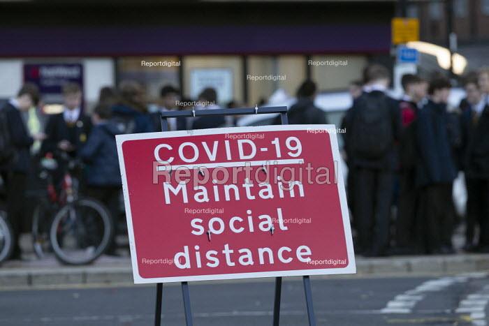 Pupils socialising, bus stop by Covid-19 Maintain Social Distance sign, Stratford Upon Avon, Warwickshire - John Harris - 2020-11-10