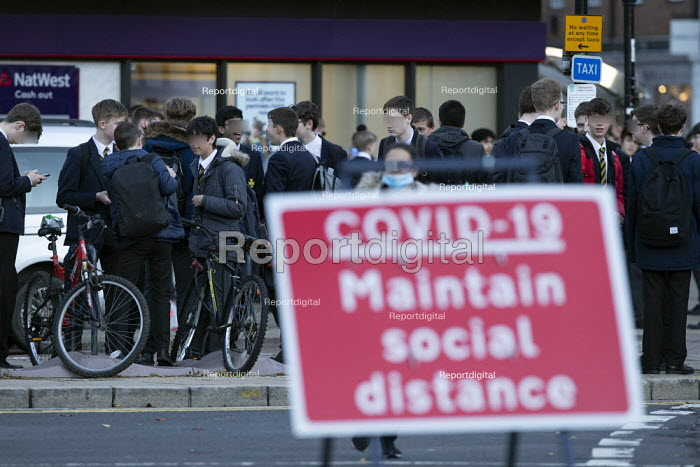 Pupils socialising, bus stop by Covid-19 Maintain Social Distance sign, Stratford Upon Avon, Warwickshire. Faces blurred - John Harris - 2020-11-10