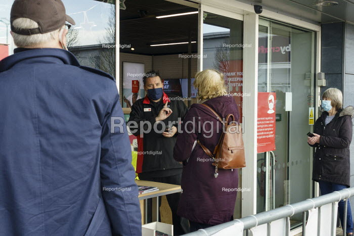 Customers being served at the door, Argos, Maybird Shopping Centre, Stratford upon Avon, Warwickshire. Shopworker serving through the front door to a socially distanced queue of shoppers - John Harris - 2020-11-24
