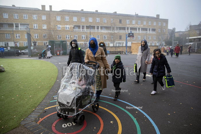 Parents bringing children to school wearing face masks, Lansbury Lawrence Primary School during Covid pandemic lockdown, Poplar, East London. - Jess Hurd - 2020-11-27