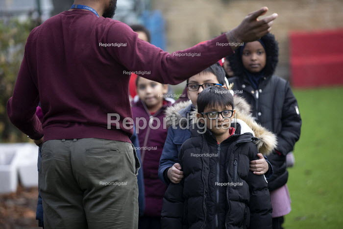 Teacher and pupils studying rock formations in the playground, Lansbury Lawrence Primary School during Covid pandemic lockdown, Poplar, East London. - Jess Hurd - 2020-11-27
