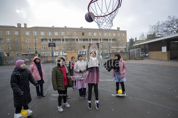 Shooting basketball hoops, breaktime in the playground, Lansbury Lawrence Primary School during Covid pandemic lockdown, Poplar, East London. - Jess Hurd - 2020-11-27